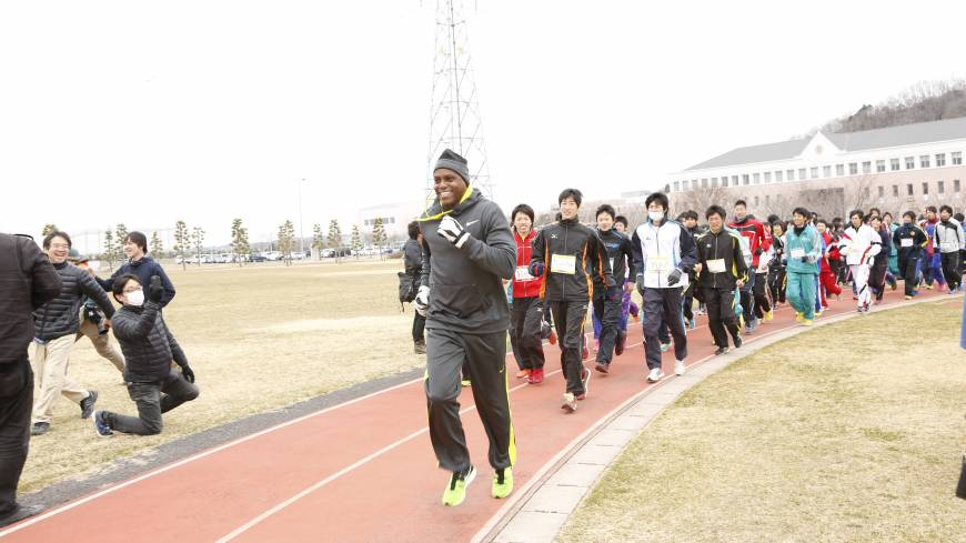 Getting pointers from a superstar: Olympic legend Carl Lewis trains with youth athletes on Sunday as part of the two-day 'Tohoku Sports Summit.' COURTESY | PHOTO