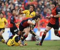 Spirited competition: Sanyo Wild Knights wing Takashi Miyake wins the ball from Suntory Sungoliath defenders during the 46th All-Japan Rugby Championship on Saturday at Prince Chichibu Memorial Rugby Ground. Sanyo rallied for a 24-16 triumph. | YUKA SHIGA
