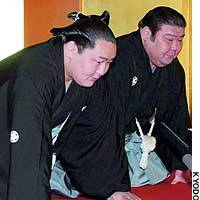 Asashoryu (left) bows with stablemaster Takasago as sumo officials notify the Mongolian wrestler of his promotion to yokozuna.