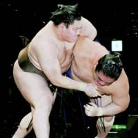 Yokozuna Hakuho (left) remains unbeaten by defeating maegashira No. 4 Wakanosato on the ninth day of the New Year Grand Sumo Tournament at Tokyo's Ryogoku Kokugikan on Monday. | KYODO PHOTO