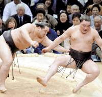 Yokozuna Asashoryu forces sekiwake Ama out of the ring on Monday to stay undefeated in the Spring Grand Sumo Tournament at Osaka Perfectural Gymnasium. | KYODO PHOTO