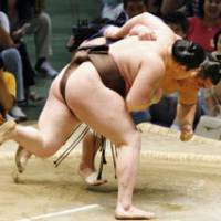 Building momentum: Yokozuna Hakuho throws fourth-ranked maegashira Wakanosato on Monday to continue his unbeaten run at the Nagoya Grand Sumo Tournament at Aichi Prefectural Gymnasium. | KYODO PHOTO