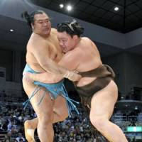 Wounded lion: Yokozuna Hakuho (right) gets to grips with top-ranked maegashira Toyonoshima at the Kyushu Grand Sumo Tournament on Monday. | KYODO PHOTO