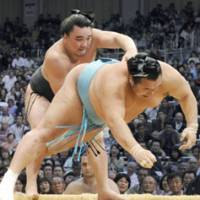 Got there in the end: Sekiwake Ama recovers from a sluggish start to dump No. 1 maegashira Toyonoshima out of the ring at the Kyushu Grand Sumo Tournament on Sunday. | KYODO PHOTO