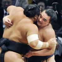 Brute force: Ama and Chiyotaikai lock horns at the Kyushu Grand Sumo Tournament on Wednesday. Ama won the bout to stay one victory behind leader Hakuho. | KYODO PHOTO