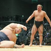 Last man standing: Ama stands over Kotomitsuki after beating the ozeki at the Kyushu Grand Sumo Tournament on Saturday to maintain a share of the lead with yokozuna Hakuho going into the final day.   KYODO PHOTO