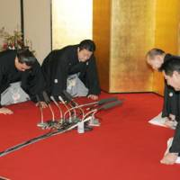 Ama (second from left) bows with stablemaster Isegahama and his wife as sumo officials notify the Mongolian wrestler of his promotion to ozeki on Wednesday in Fukuoka.   KYODO PHOTOS