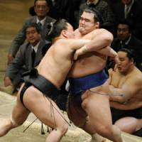 Off the mark: Harumafuji (left) heaves Kotoshogiku out of the ring as Asashoryu watches on at the New Year Grand Sumo Tournament on Thursday. | KYODO PHOTO