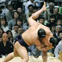 On the brink: Tochiozan pushes Harumafuji to the limit at the Spring Grand Sumo Tournament on Friday.   KYODO PHOTO