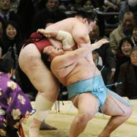 Gritty spirit: Toyonoshima (right) endures a throw by Yamamotoyama on the 13th day of the Spring Grand Sumo Tournament in Osaka on Friday. | KYODO PHOTO