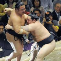 Strictly business: Asashoryu takes care of Chiyotaikai at the Summer Grand Sumo Tournament on Monday.   KYODO PHOTO