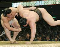 Mongolian ozeki Harumafuji (left) unleashes a lower-arm throw to yokozuna Hakuho, who defeated Harumafuji on Friday, in a playoff to clinch his first Emperor's Cup on the final day of the Summer Grand Sumo Tournament on Sunday at Tokyo's Ryogoku Kokugikan. Story: Page 15. | KYODO PHOTO