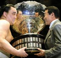 Special honor: Mongolian ozeki Harumafuji, formerly known as Ama, receives the Prime Minister's Cup from Taro Aso after beating yokozuna Hakuho in a playoff to win the Summer Grand Sumo Tournament on Sunday at Ryogoku Kokugikan.