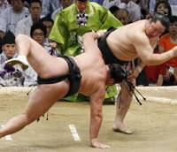 One down: Asashoryu hurls Kyokutenho to the ground on the opening day of the Nagoya Grand Sumo Tournament at Aichi Prefectural Gymnasium on Sunday. | KYODO PHOTO