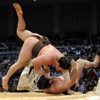 Sole leader: Yokozuna Hakuho (top) showcases his strength against Kotooshu on Friday in the Kyushu Grand Sumo Tournament. | KYODO PHOTO