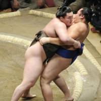 Lean on me: Hakuho forces Kakuryu out of the ring at the New Year Grand Sumo Tournament on Sunday. | KYODO PHOTO