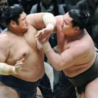 Close call: Yokozuna Hakuho (right) competes against Kotomitsuki during their bout on Thursday at the Spring Grand Sumo Tournament in Osaka. | KYODO PHOTO