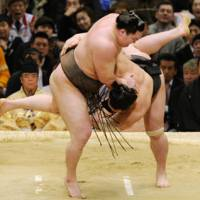 Top dog: Hakuho downs Harumafuji to win the Spring Grand Sumo Tournament with a perfect record on Sunday.   KYODO PHOTO