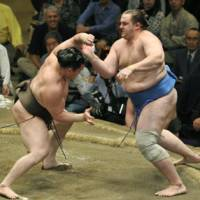 Clash of the titans: Hakuho and Baruto tussle at the Summer Grand Sumo Tournament on Thursday. | KYODO PHOTO