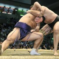 Locked up: Hakuba feels the strain as Kotooshu moves in for victory at the Nagoya Grand Sumo Tournament on Monday. | KYODO PHOTO