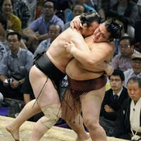 Show of strength: Ozeki Kotooshu forces Kisenosato out of the ring during the Nagoya Grand Sumo Tournament on Saturday. | KYODO PHOTO