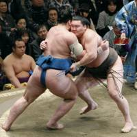 Brute force: Hakuho and rank-and-filer Tamawashi (left) square off on the eighth day of the New Year Grand Sumo Tournament at Ryogoku Kokugikan.   KYODO PHOTO