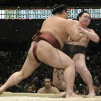 Got your number: Kisenosato applies the final touch to push Hakuho out of the ring at the New Year Grand Sumo Tournament on Wednesday.   KYODO PHOTO