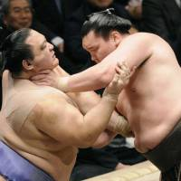 All in hand: Hakuho (right) gets a grip on Kaio's throat on the final day of the New Year Grand Sumo Tournament in Tokyo on Sunday. | KYODO PHOTO