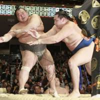 Show of force: Kakuryu (right) improves to 3-0 in the New Year Grand Sumo Tournament with a win over Toyonoshima on Tuesday at Tokyo's Ryogoku Kokugikan.   KYODO
