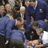 Scary moment: Referee Shozaburo Kimura is attended to by officials after taking a fall during the fourth day of the New Year Grand Sumo Tournament on Wednesday. | KYODO
