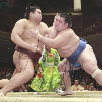 No job for the timid: Kotoshogiku (right) pushes Takayasu out of the ring at the New Year Grand Sumo Tournament on Saturday. | KYODO
