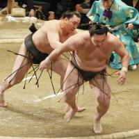 Shown the door: Harumafuji (left) shoves Hakuho out of the ring at the New Year Grand Sumo Tournament on Thursday. | KYODO