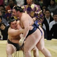 Crouching tiger: Hakuho (left) beats Tochinoshin at the Spring Grand Sumo Tournament on Sunday. | KYODO