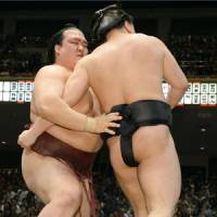 Back on track: Kisenosato (left) pushes Harumafuji out of the ring at the Summer Grand Sumo Tournament on Saturday. | KYODO