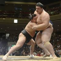 Ozeki Harumafuji has a firm grip on Aoiyama's mawashi as he pushes him out of the ring on the opening day of the Autumn Grand Sumo Tournament. | KYODO PHOTO