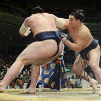 Staying aggressive: Ozeki Harumafuji (right) shoves komusubi Tochinoshin out of the raised ring at the Autumn Grand Sumo Tournament on Thursday. Harumafuji improved to 5-0. | KYODO