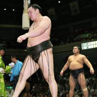 Disappointed: Yokozuna Hakuho (front) walks out of the ring after a loss to Tochiozan on Tuesday at the Autumn Grand Sumo Tournament in Tokyo.   KYODO
