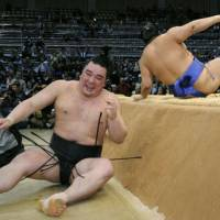 Sudden impact: Harumafuji (left) hits the floor after being thrown from the ring by Okinoumi at the Kyushu Grand Sumo Tournament on Monday. | KYODO