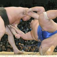 Still the leader: Yokozuna Hakuho overpowers Kotoshogiku on Thursday at the Kyushu Grand Sumo Tournament. | KYODO