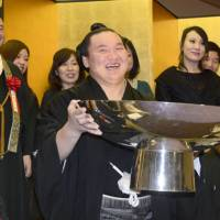 Another year over: Hakuho celebrates victory at the Kyushu Grand Sumo Tournament in Fukuoka on Sunday. | KYODO