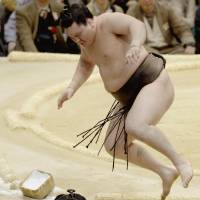 Watch out below: Hakuho jumps out of the falls out of the ring after defeating Myogiryu on Wednesday. | KYODO