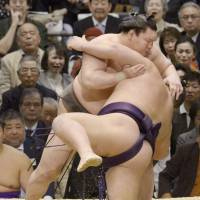 Taking care of business: Yokozuna Hakuho overpowers Chiyotairyu on Friday at the Spring Grand Sumo Tournament in Osaka. | KYODO