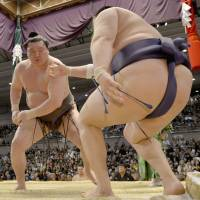 Laying down the law: Hakuho (left) takes on Tokitenku at the Spring Grand Sumo Tournament in Osaka on Saturday. | KYODO