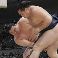Cruising along: Yokozuna Hakuho (left) picks up his 14th victory in as many bouts in the Spring Grand Sumo Tournament on Saturday. | KYODO