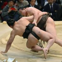 Top class: Hakuho (right) takes down Harumafuji on the final day of the Spring Grand Sumo Tournament on Sunday. | KYODO