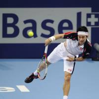 Soaring: Kei Nishikori serves to Kazakhstan's Mikhail Kukushkin in their quarterfinal match at the Swiss Indoors on Friday night. Nishikori won 6-4, 5-7, 6-4. | AP PHOTO