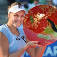 Breakthrough: Russia's Nadia Petrova holds up her prize after beating Poland's Agnieszka Radwanska 6-0, 1-6, 6-3 in the final of the Pan Pacific Open on Saturday at Ariake Colosseum.   AFP-JIJI