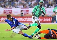Nigeria Goalkeeper Greg Etafia makes a save at the feet of Japan striker Atsushi Yanagisawa.