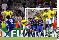 Shunsuke Nakamura of Japan hits a free-kick over the Brazilian wall during their Confederations Cup game in Cologne, Germany, on Wednesday. The match ended 2-2.