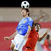 Yuki Abe, left, battle a Bahrani player for the ball during their World Cup qualifier on Manama on Wednesday. Bahrain won 1-0. | KYODO PHOTO